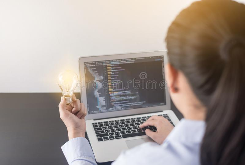 Young woman programmer hand holding light bulb, woman hands coding and programming on screen laptop, new ideas with innovation. stock photos