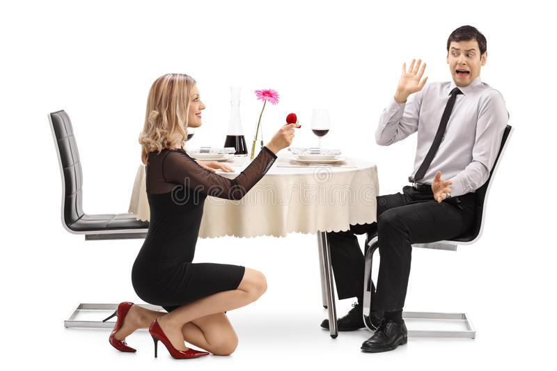Young woman proposing to her shocked boyfriend. Young women proposing to her shocked boyfriend at a restaurant table isolated on white background royalty free stock image