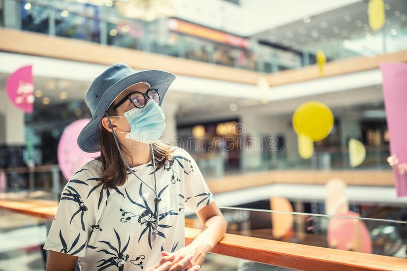 Young woman is protected from coronavirus with a protective mask in the interior of the supermarket stock images