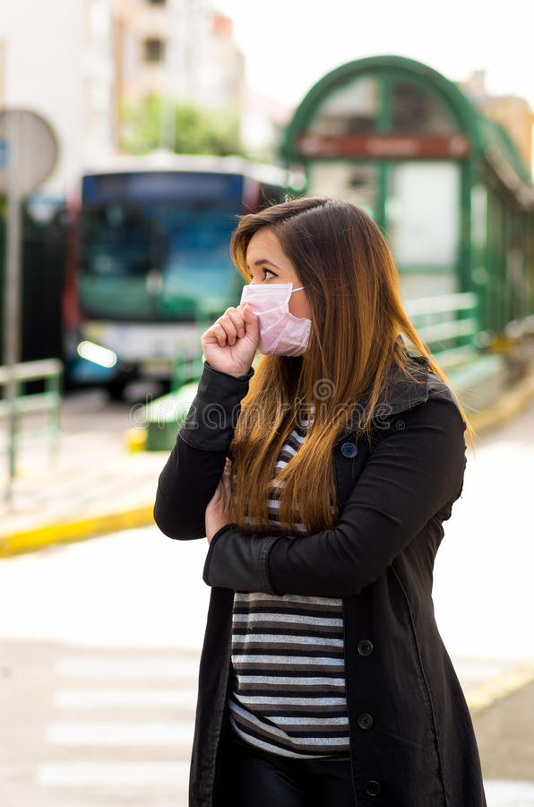 Young woman with protective mask coughing on the street in the city with air pollution, blurred public transport. Background stock image