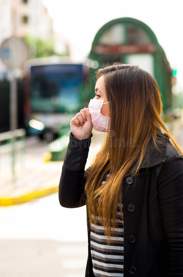 Young woman with protective mask coughing on the street in the city with air pollution, blurred public transport. Background stock photos
