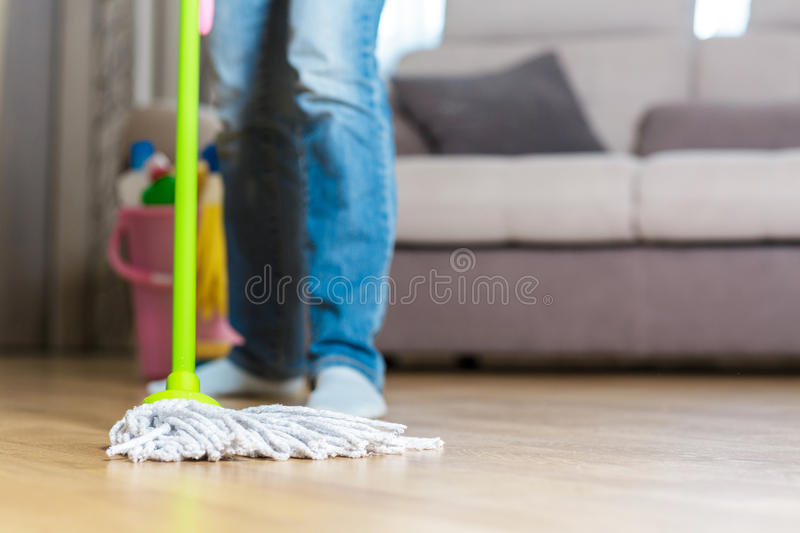 Woman in protective gloves using a wet-mop while cleaning floor royalty free stock photography
