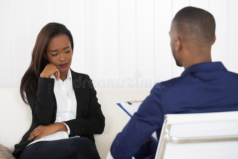 Young Woman And Psychiatrist. Depressed African American Woman At Psychiatrist Appointment royalty free stock image