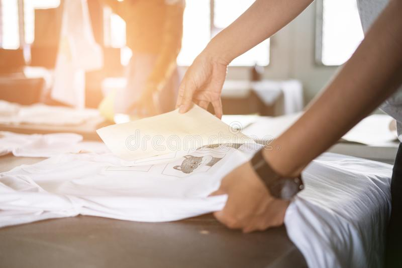 Young woman pull out paper from waterproof film on fabric at shop. worker working on manual screen printing on t-shirt. stock image