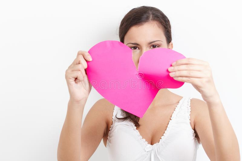 Young woman pulling paper heart to pieces stock photos