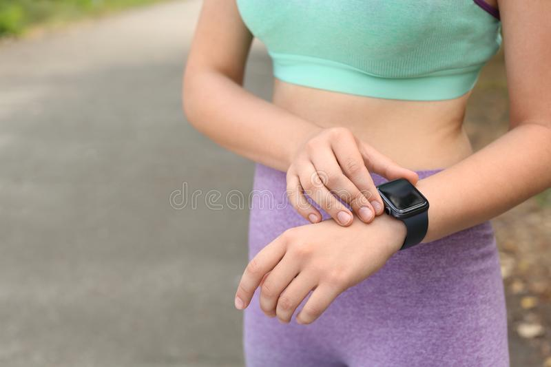 Young woman  pulse with smartwatch after training on street, closeup. Space for text stock photos