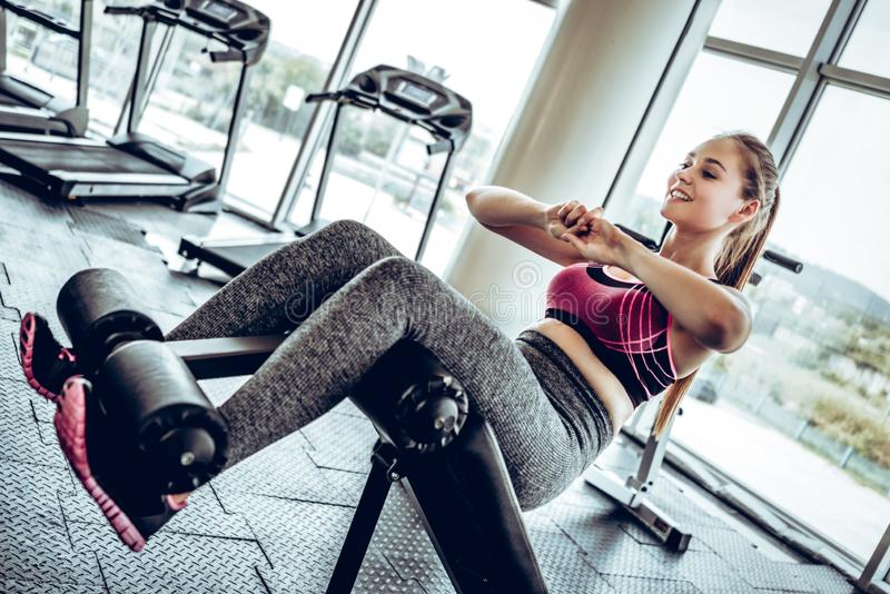 A young woman pumping a press on a simulator in a gym. royalty free stock photo