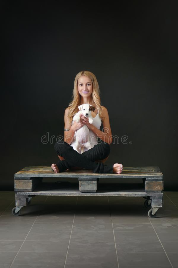 Young woman with puppy in yoga pose royalty free stock image