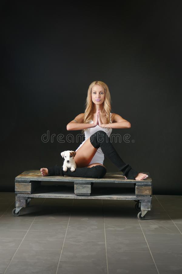 Young woman with puppy in yoga pose stock photo