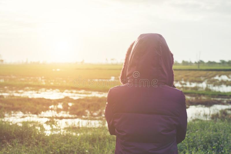 Young woman in a purple down jacket winter view from the back,during sunset. royalty free stock images