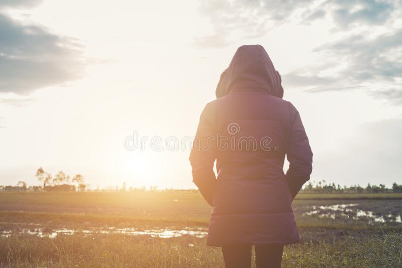 Young woman in a purple down jacket winter view from the back,during sunset. stock image