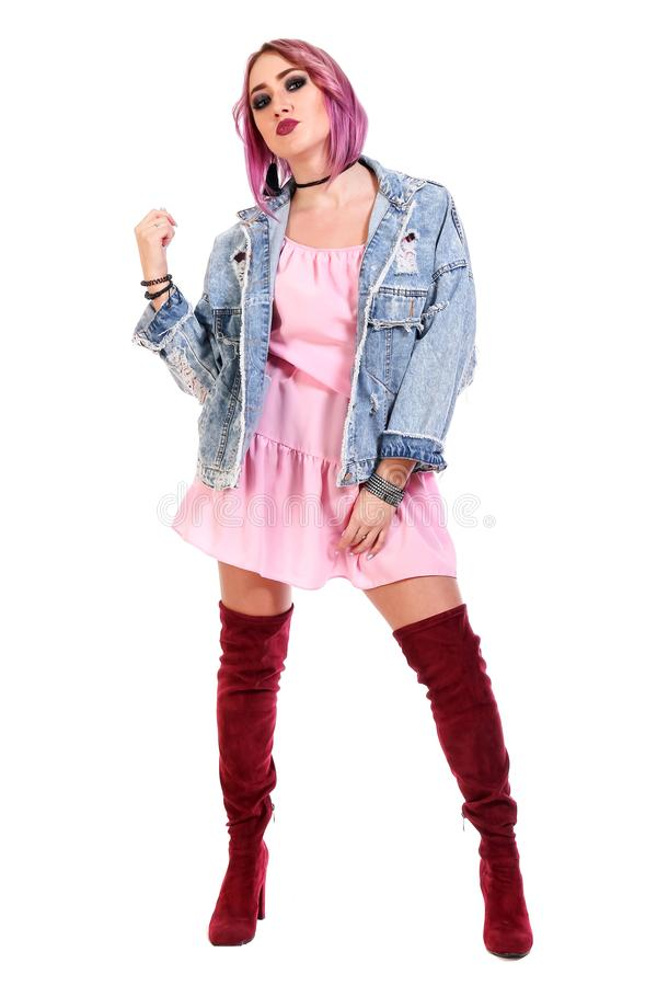 Young woman with a purple hair in a pink dress and jeans jacket royalty free stock photography