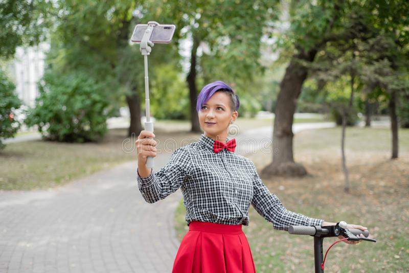 A young woman with purple hair rides an electric scooter in a park. Stylish girl with a shaved temple in a plaid shirt. A long red skirt and a bow tie takes a royalty free stock photo