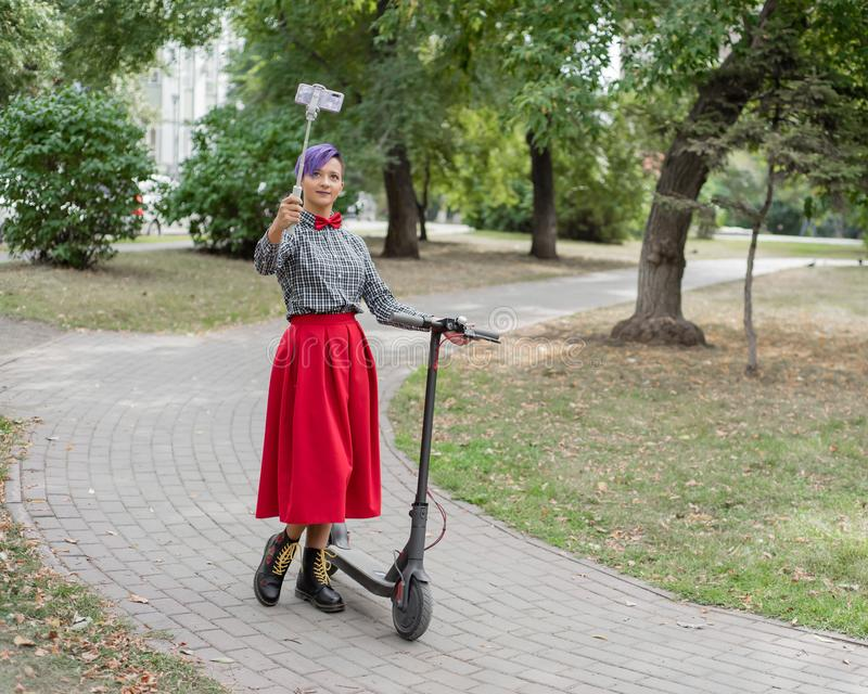 A young woman with purple hair rides an electric scooter in a park. Stylish girl with a shaved temple in a plaid shirt. A long red skirt and a bow tie takes a royalty free stock images