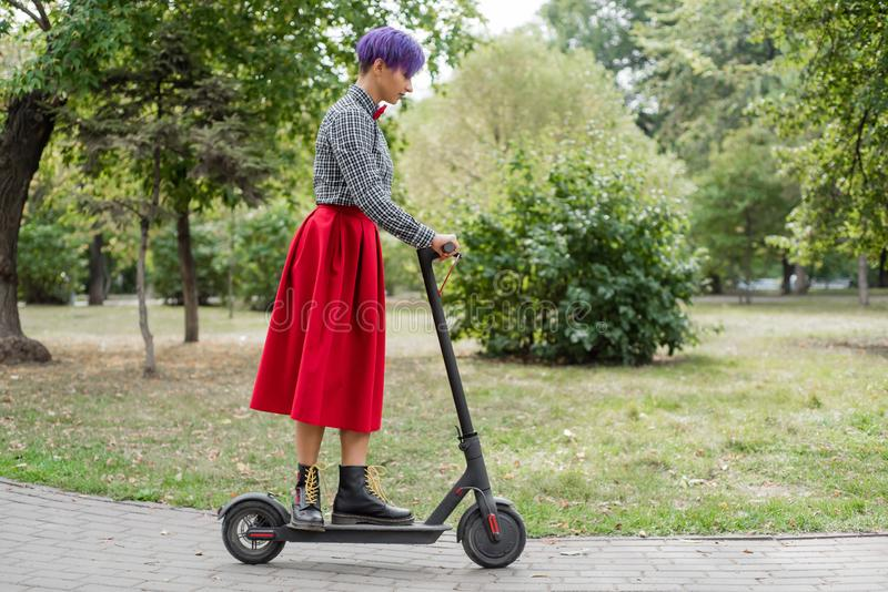 A young woman with purple hair rides an electric scooter in a park. A stylish girl with a shaved temple in a plaid shirt. A long red skirt and a bow tie is stock photography