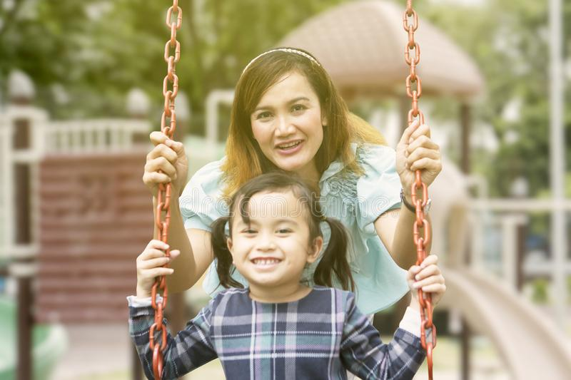 Young woman pushes her daughter on the swing. Image of young women pushing her daughter on the swing while playing in the playground stock images