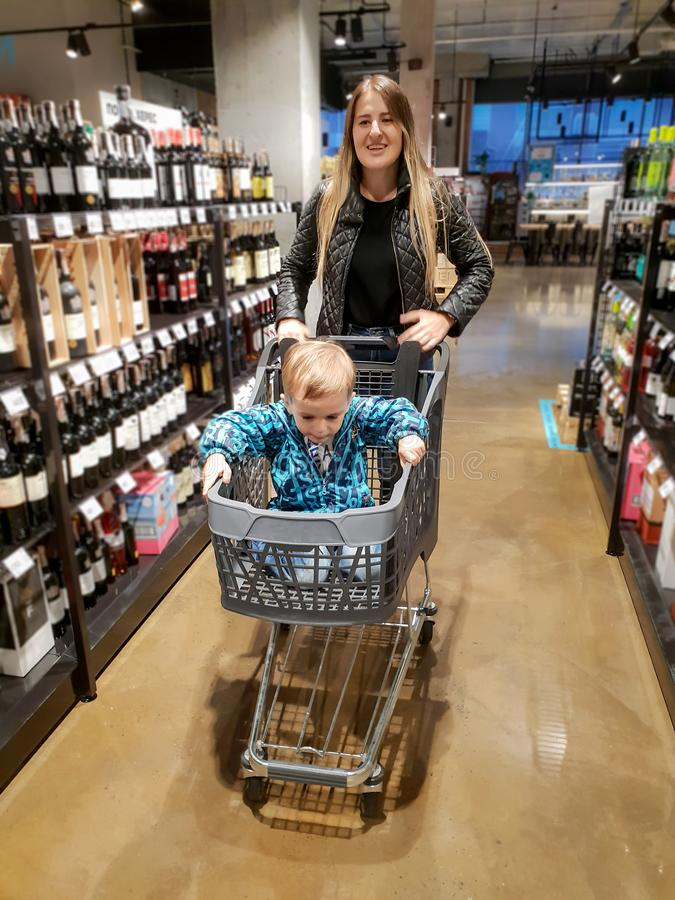 Beautiful young woman pushing shopping cart in store between shelves with food and drinks while her little son sitting royalty free stock image
