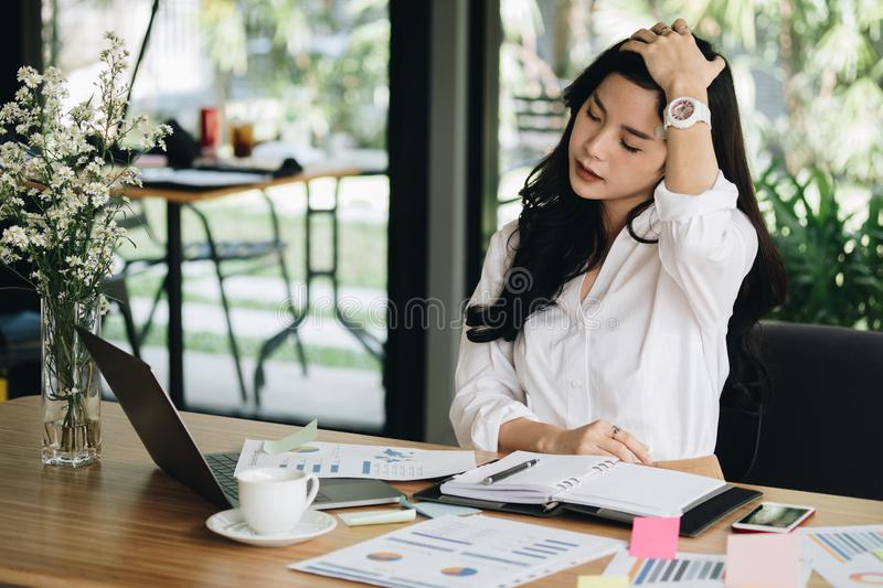 young woman put hand on head feeling tired, frustrated & stressed from hard work at office. exhausted businesswoman have headache stock photography