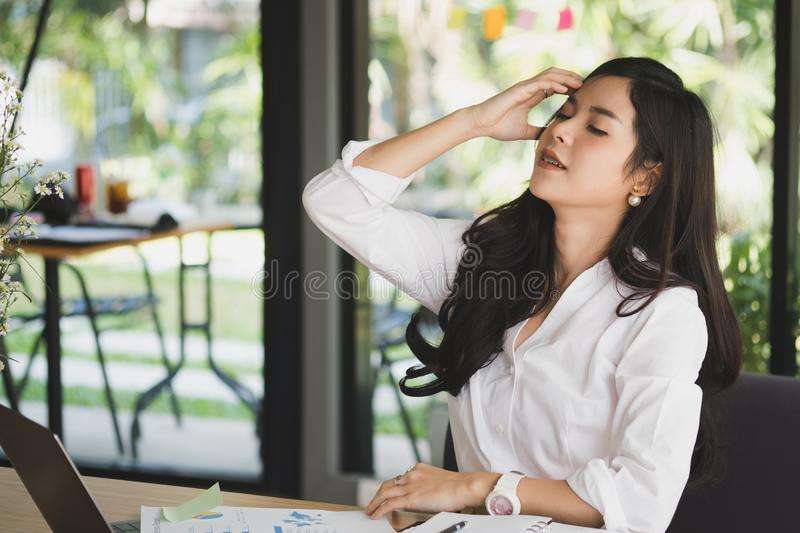 young woman put hand on head feeling tired, frustrated & stressed from hard work at office. exhausted businesswoman have headache stock photo