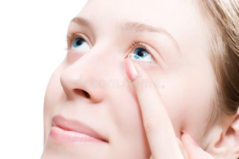 Young woman puting a contact lens royalty free stock photos