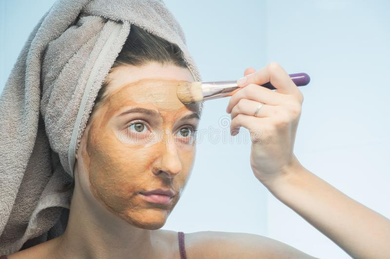 A young woman puts a clay mask on her face with a brush in bathroom. stock photos