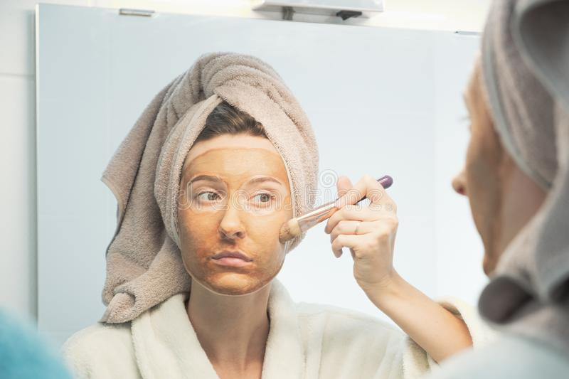 Young woman puts clay mask on her face with brush looking in mirror in bathroom. royalty free stock photography