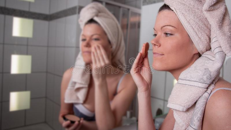 Young woman puts on make up stock images