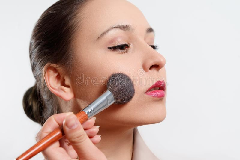 A young woman puts makeup on her face with a brush. on white background royalty free stock images