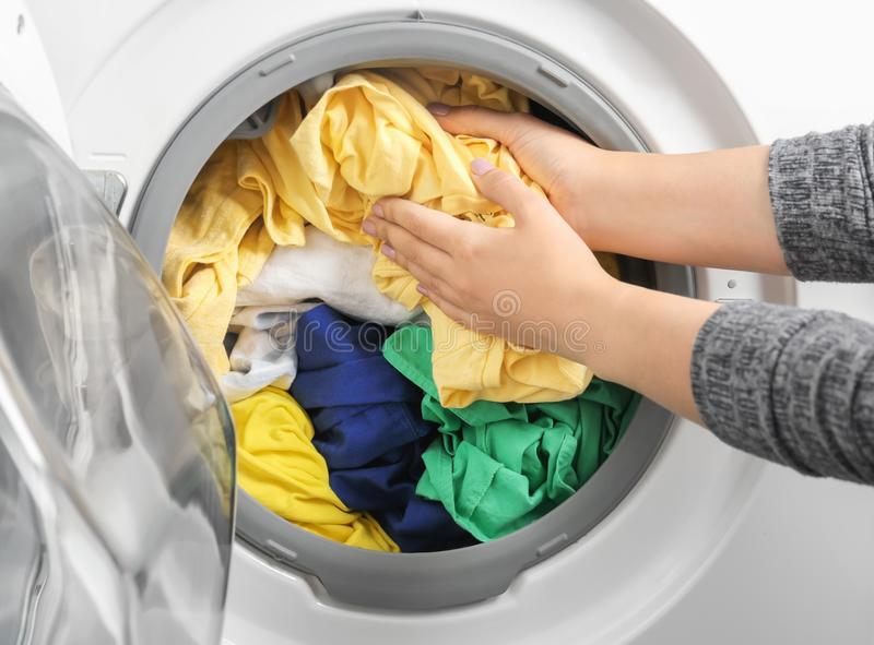 Young woman putting clothes into washing machine stock image