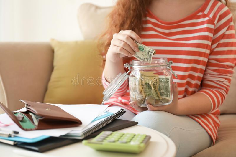 Young woman putting dollar banknote into glass jar indoors. Money savings concept stock photos
