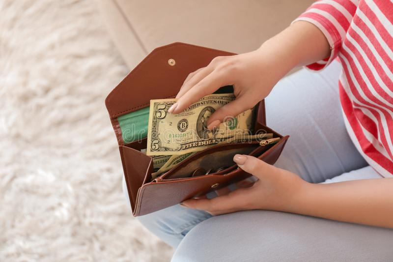 Young woman putting dollar banknote into wallet indoors, closeup. Money savings concept stock image