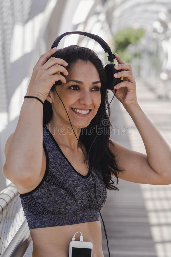 Young woman putting on headphones stock images