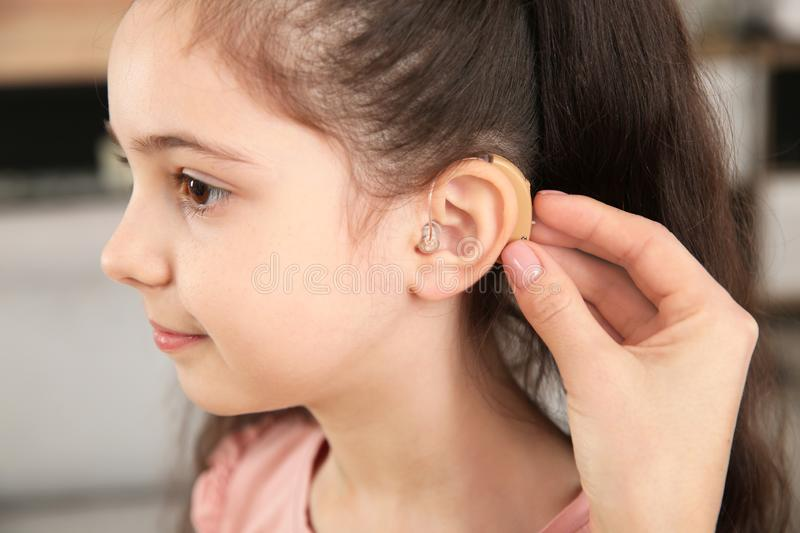 Young woman putting hearing aid in daughter`s ear indoors. Closeup stock image