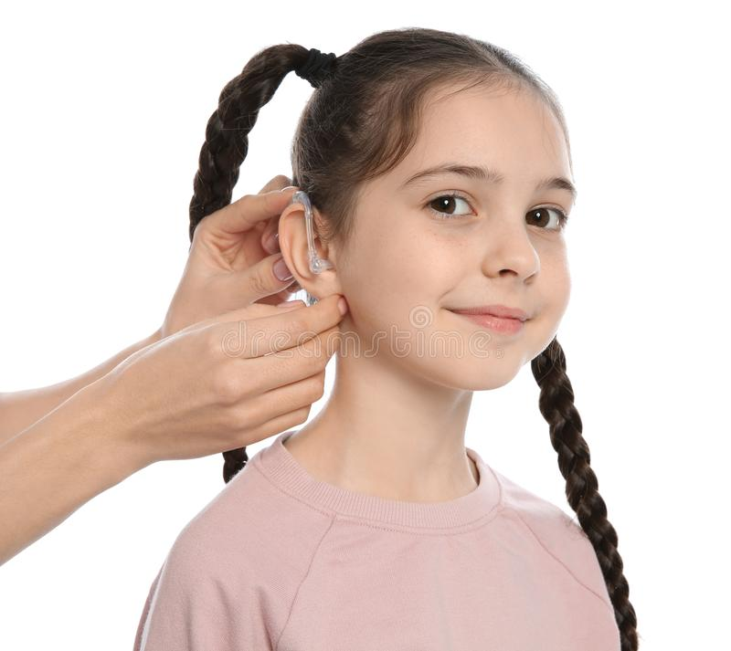 Young woman putting hearing aid in little girl`s ear on white. Background royalty free stock photo