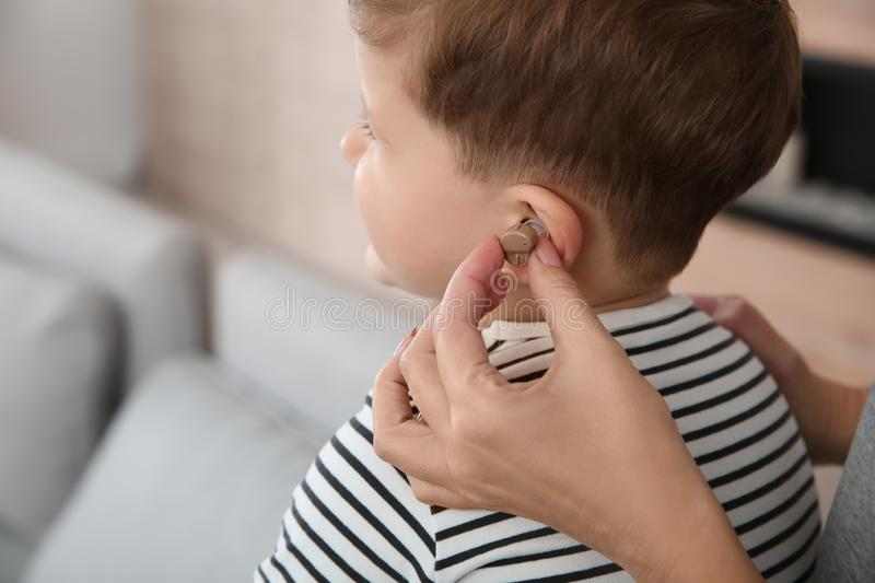 Young woman putting hearing aid in little son`s ear, closeup stock image