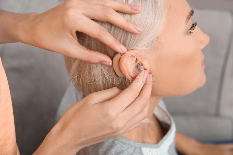 Young woman putting hearing aid in mother`s ear indoors. Closeup stock photos