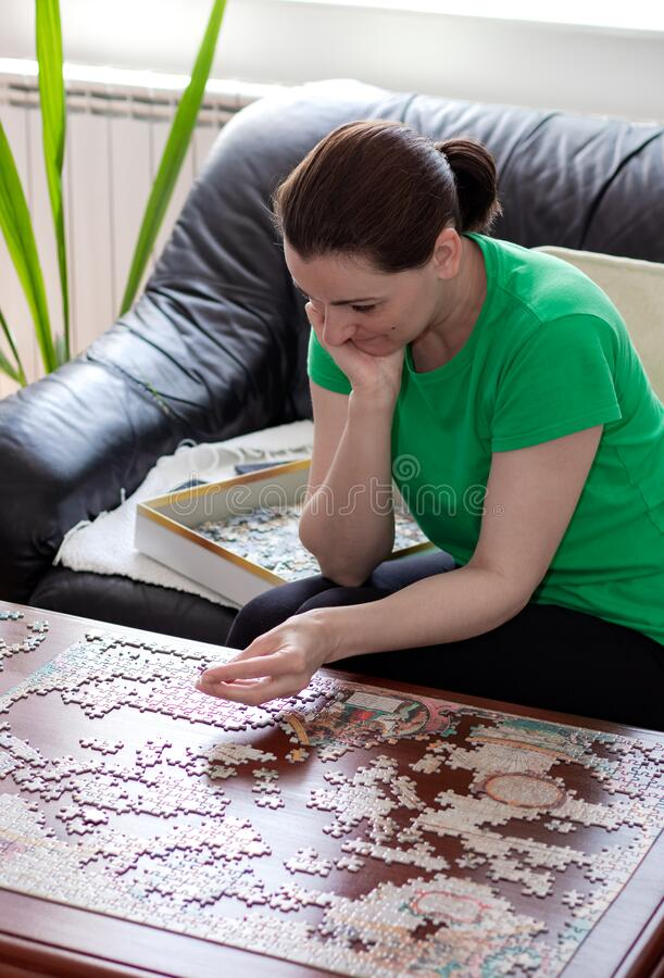 Free Young Woman Putting Jigsaw Puzzle Pieces Together. Royalty Free Stock Images - 180028969