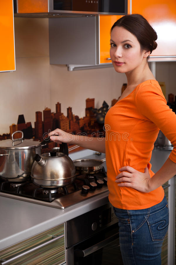 A young woman is putting a kettle royalty free stock images