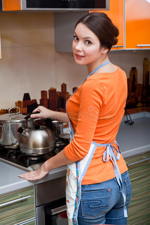 A young woman is putting a kettle stock image