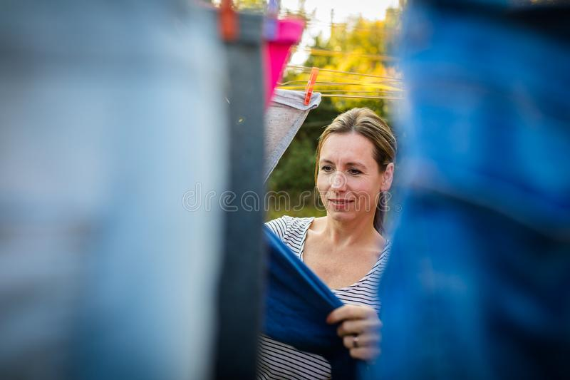 Young woman putting laundry on a rope in her garden royalty free stock photography