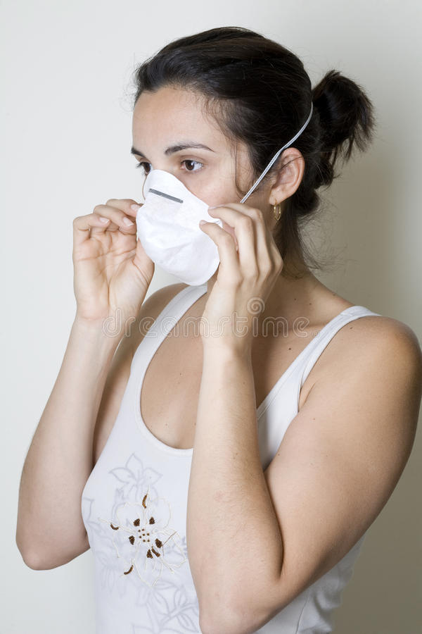 Download Young Woman Putting On A Mask Against Swine Flu Stock Image - Image: 9630691