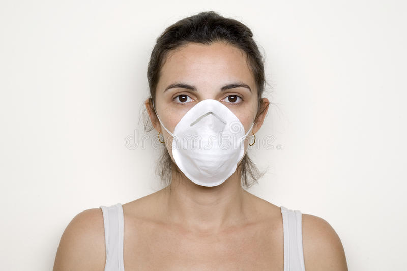 Young Woman Putting On A Mask Against Swine Flu Royalty Free Stock Photos
