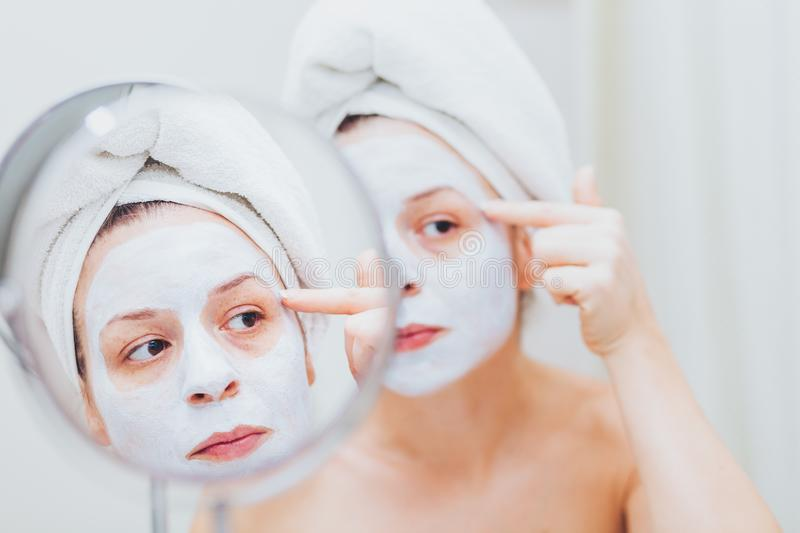 Young woman putting a mask on her face stock images