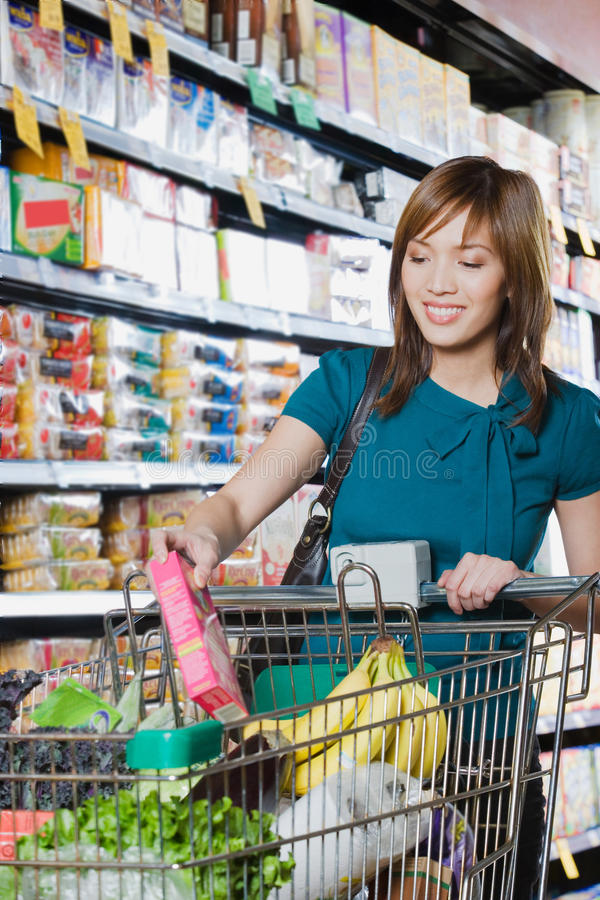 Young woman putting a packet in a shopping trolley. Young women putting a packet in a shopping trolley royalty free stock images