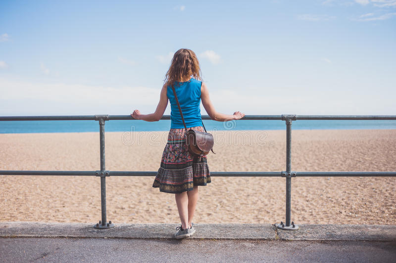Young woman by railing on the beach. A young woman is standing by a railing on the beach on a sunny day royalty free stock photo