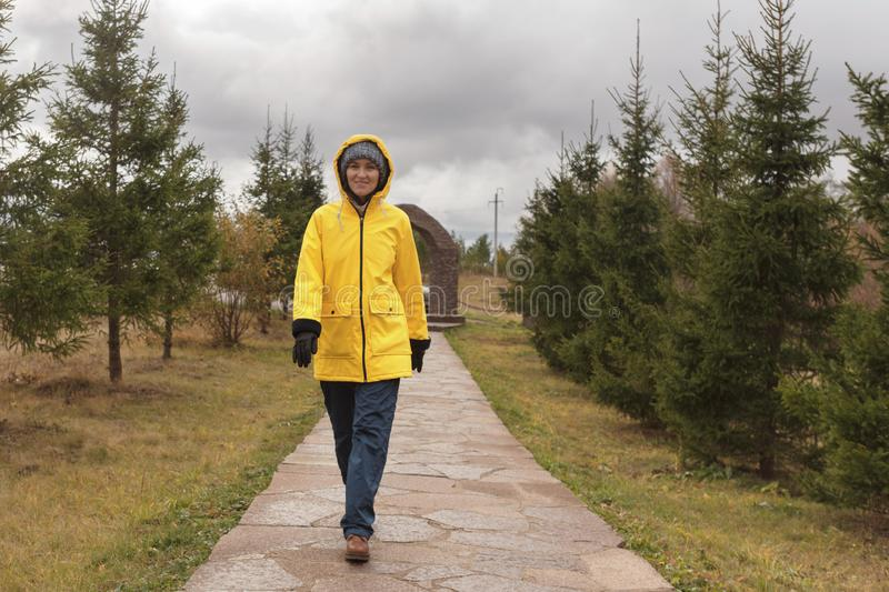 Young woman in raincoat walks in park in cloudy weather, copy space. Young woman in a yellow raincoat walking along the path in the Park in cloudy weather royalty free stock image