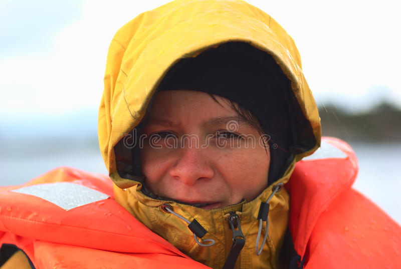 Young Woman in Rainy Weather on a Boat. Young woman in rainy weather wearing a rainjacket and a life jacket on a boat (Selective Focus, Focus on the left eye of royalty free stock photography