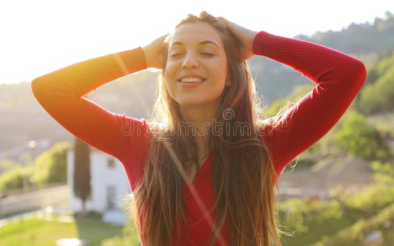 Young woman with raised arms enjoying spring breeze in the park. The sun is shining.  stock photo