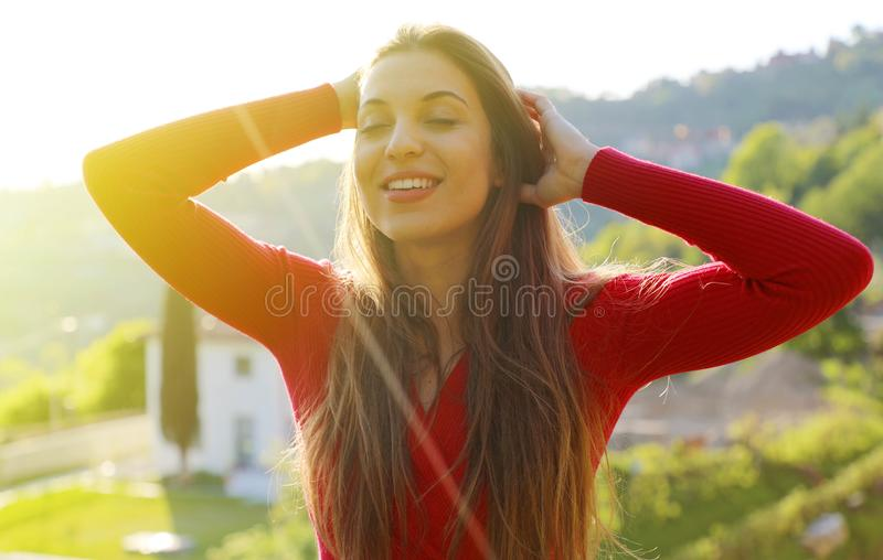 Young woman with raised arms enjoying spring breeze in the park. The sun is shining.  stock photos