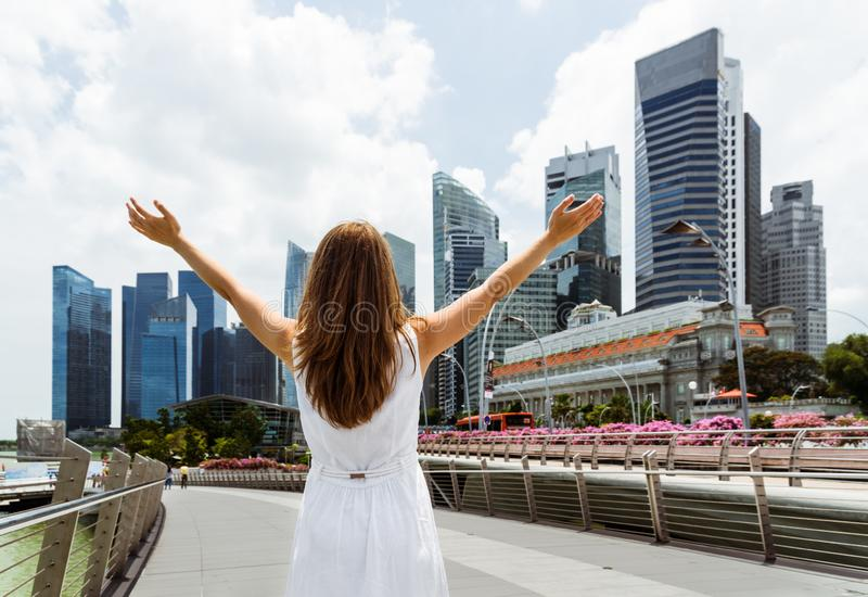 Young woman with raised arms on skyscrapers background royalty free stock photo
